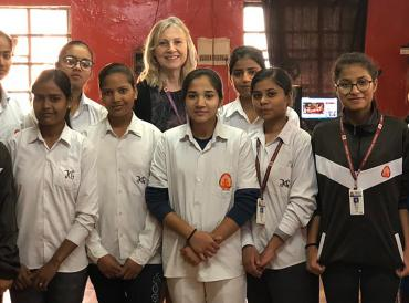 The Chief Examiner with a dozen young female students in a school in India