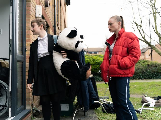Two women standing outside a house holding a toy panda, taken from LAMDA short film St Christopher and featuring grads Esme Scarborough and Matilda Tucker